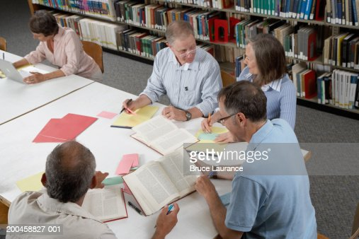 People gathered around table in library, elevated view : Stock Photo