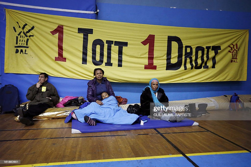People gathered by the French association Droit au Logement (Right to Housing) sit in front of a banner that reads '1 Roof, 1 Right' on February 17, 2013 in Paris as they and over 200 others occupy a municipal gymnasium to demand that City Hall house them.
