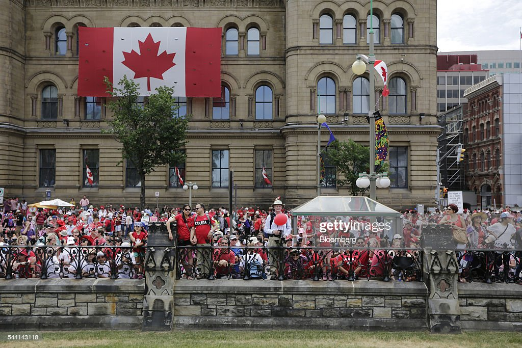 People gathered outside the gates of Parliament Hill on Canada Day in Ottawa, Ontario, Canada, on Friday, July 1, 2016. On July 1, thousands of locals and tourists gather in Ottawa's downtown area to celebrate. This year marks Canada's 149th birthday and Trudeau's first Canada Day as Prime Minister. Photographer: David Kawai/Bloomberg via Getty Images