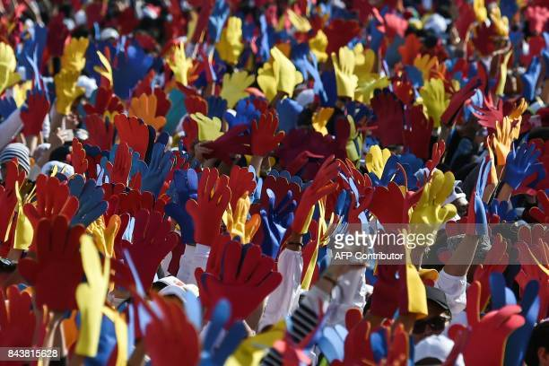 People gathering at Bolivar Square wave big gloves in the Colombian colours listen as Pope Francis appears at abalcony of the Archbishop's Palace in...