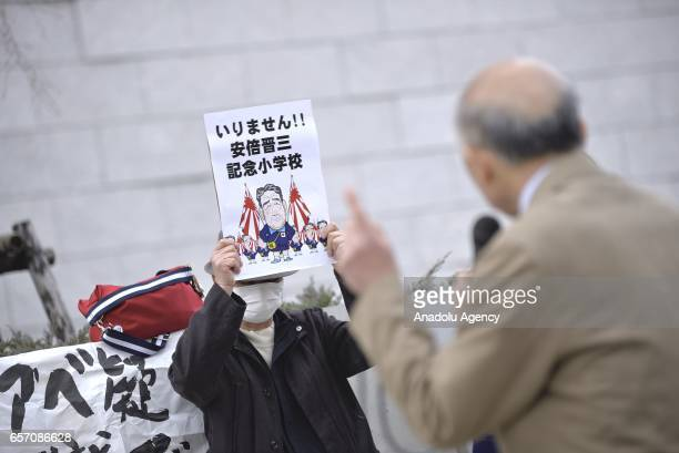 People gathering near the Japan Parliament hold placards against Japanese Prime Minister Shinzo Abe as Yasunori Kagoike head of the Moritomo Gakuen...