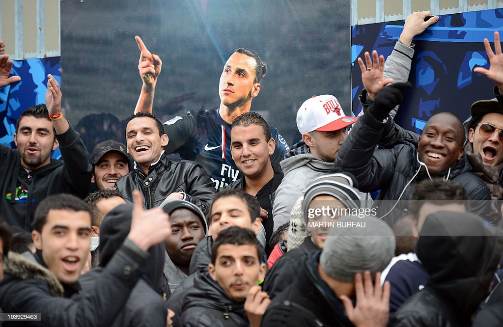 People gesture as they queue up in front of the Paris Parc des Princes stadium, on March 18, 2013 in Paris, to buy tickets to attend the Champions League quarter final match between Paris Saint-Germain and FC Barcelone scheduled on April 2, in this stadium. At background, a poster of Paris' Swedish forward Zlatan Ibrahimovic.