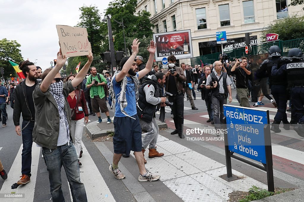 People gesture as they take part in a demonstration against controversial labour reforms, on June 28, 2016 in Paris. Unions have called repeated strikes and marches in opposition to the law, which seeks to bring down France's intractable 10-percent unemployment rate by making it easier to hire and fire workers. / AFP / Thomas SAMSON