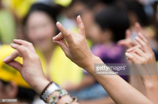 People gestures as they look at performers dressed as Pikachu a character from Pokemon series game titles during a parade as part of the Pikachu...
