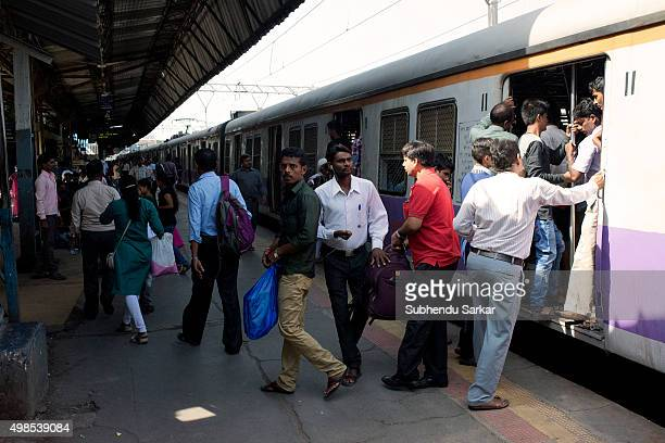 People get down on a platform from a local train in Mumbai