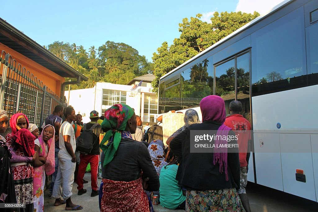People get into a bus on May 29, 2016 in Ouangani, center part of the French overseas region and department Mayotte, to go to the capital, Mamoutzou. Around 500 'illegal immigants', mostly from Comoros, evicted from their house by local Mayotte inhabitants, camp out since May 15, 2016 on Republique square at Mamoudzou as associations try to rehouse them. Rising anti-migrant anger has seen groups of up to 100 men gather in villages with lists of houses belonging to foreigners and going from door to door forcing them to leave. Police have tried to prevent violence, but have been unable to stop the pressure mounting on foreigners -- including many who are living on Mayotte legally -- who have fled their homes in fear. Mayotte opted to remain under French rule when the other islands in the Comoros archipelago chose independence in 1975. / AFP / ORNELLA
