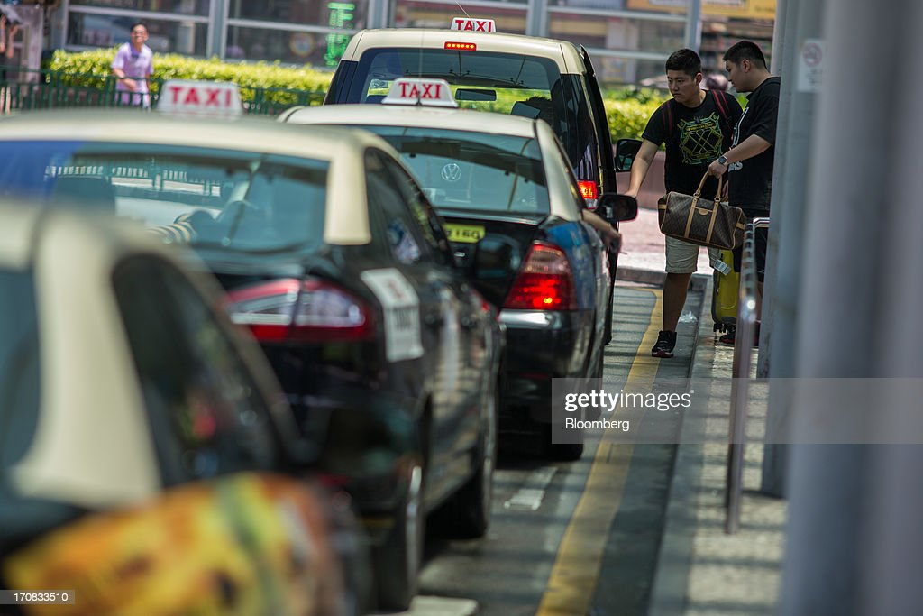 People get into a taxi after leaving the Zhuhai-Macau border crossing in Macau, China, on Tuesday, June 18, 2013. Casino revenue in Macau, the only place in China where casino gambling is legal, rose 14 percent to a record of 304 billion patacas ($38 billion) in 2012. Photographer: Lam Yik Fei/Bloomberg via Getty Images