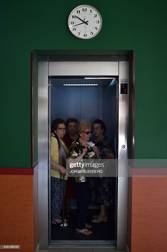 People get on in a elevator to vote in Spains general election at a polling station in cental Madrid on June 26, 2016. Spain votes today, six months after an inconclusive election which saw parties unable to agree on a coalition government. GUERRERO