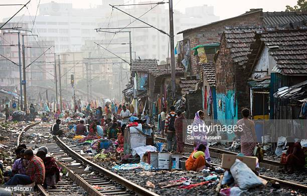 People get on with their lives in a slum on the railway tracks as a commuter train goes past on December 12 2013 in Kolkata India Almost one third of...