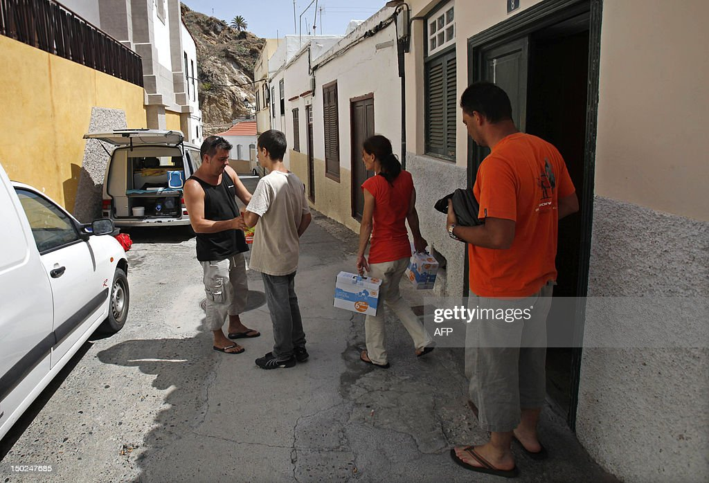 People get ready for evacuation in Vallehermoso, on August 13, 2012, on the Spanish canary island of La Gomera. Wildfires killed two people in southeastern Spain and forced thousands to evacuate in the Canary Islands where flames ravaged a rare nature reserve, authorities said Monday. AFP PHOTP / DESIREE MARTIN