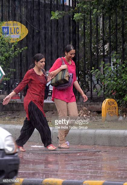 People get relief from extreme heat and enjoy in the rain on Thursday in New Delhi