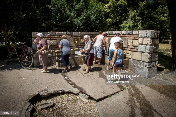 People get water from a public tap at a park in the Serbian capital Belgrade on June 25 2017 as a heat wave sweeps the country with temperatures...