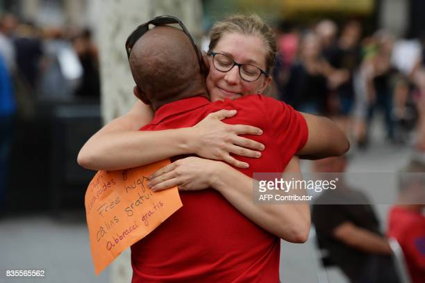 People give out free hugs on the Las Ramblas boulevard in Barcelona on August 19 two days after a van ploughed into the crowd killing 13 persons and...