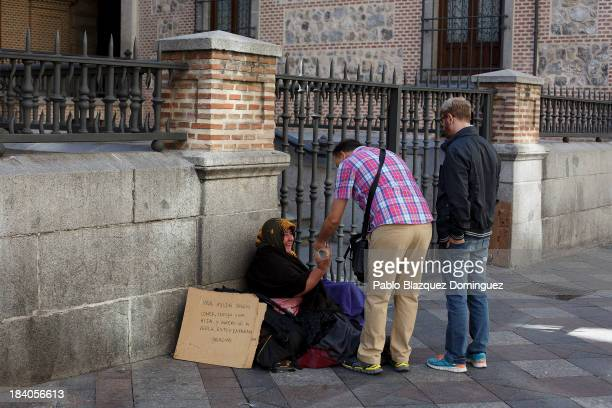 People gives alms to a beggar in the street on October 11 2013 in Madrid Spain Madrid Mayor Ana Botella and her right wing government are preparing...