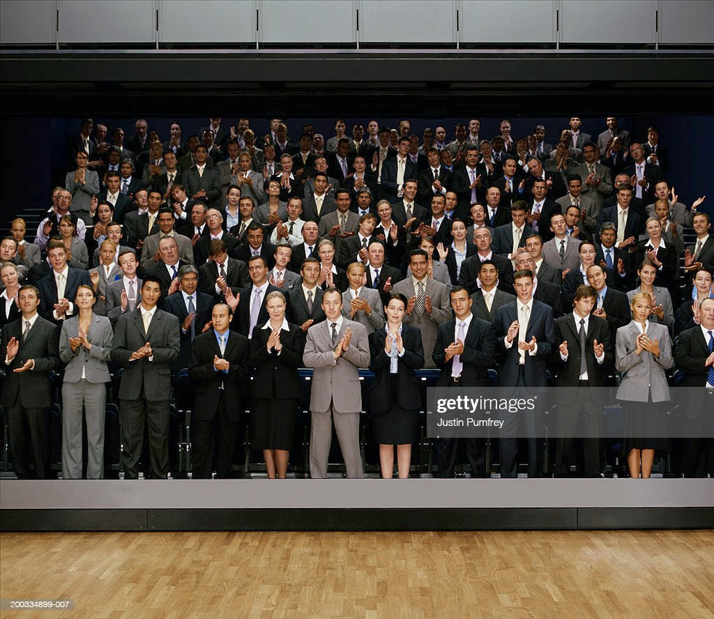 People Giving Standing Ovation In Auditorium Stock Photo