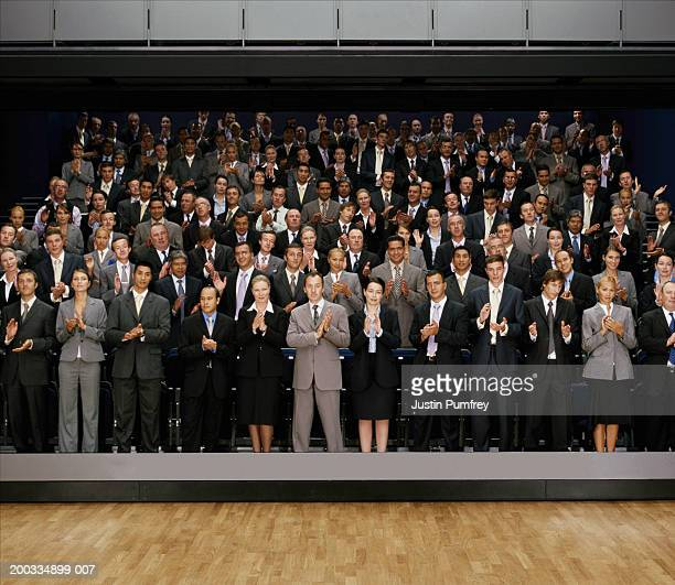 People giving standing ovation in auditorium (digital composite)
