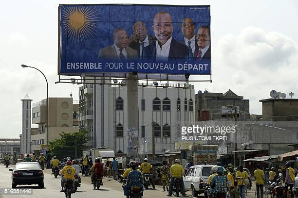 People go about with their daily life as they walk or drive cars and scooters by a billboard picturing a coalition of the opposition lead by Patrice...