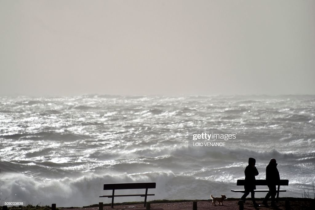 People go for a walk at the seaside in Les Sables-d'Olonne, western France, on February 9, 2016. High winds buffeted northwestern Europe on February 8, leaving one woman in France in a coma after she was hit by an advertising hoarding. Electricity was cut to 5,000 homes in northern France. / AFP / LOIC VENANCE