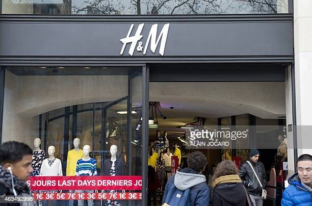 People go shopping at an HM store on February 15 2015 on the ChampsElysees avenue in Paris French lawmakers voted late February 13 in favour of...