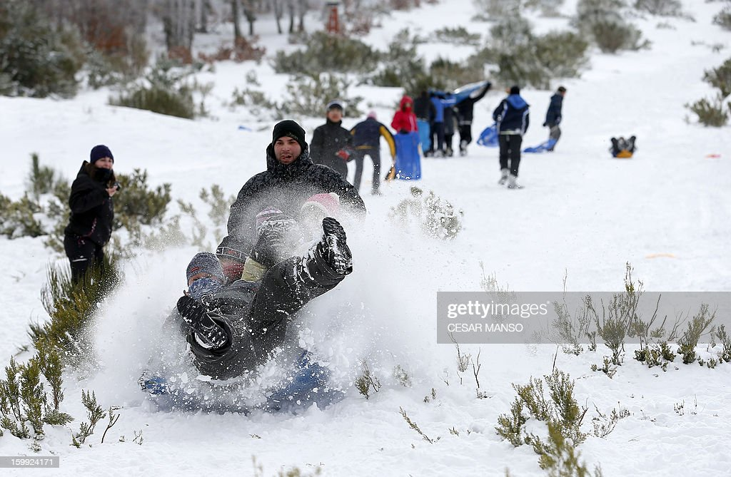 People go sledging after a snowfall in Pineda de la Sierra, near Burgos, on January 23, 2013.