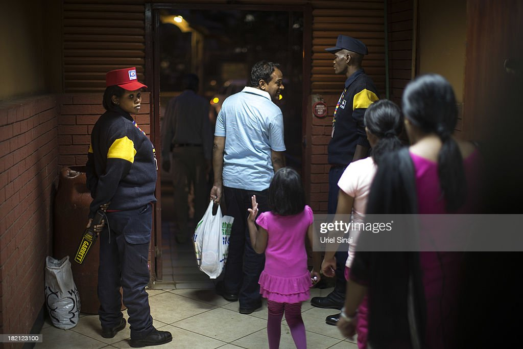 People go through security at a shopping center near the Westgate Shopping Centre on September 28, 2013 in Nairobi, Kenya. Officials begun the task of forensic probing the Westgate shopping mall following a four-day siege that killed at least 67 civilians and police and was claimed by the Somali militant group al Shabaab.