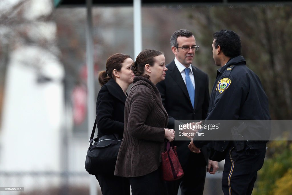 People greet a police officer as they arrive for the funeral services of six year-old Noah Pozner, who was killed in the shooting massacre in Newtown, CT, at Abraham L. Green and Son Funeral Home on December 17, 2012 in Fairfield, Connecticut. Today is the first day of funerals for some of the twenty children and seven adults who were killed by 20-year-old Adam Lanza on December 14, 2012.