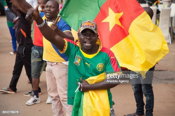 People greet as the Cameroon national team's convoy pass by during Cameroon national team's return to their home country in Yaounde Cameroon on...