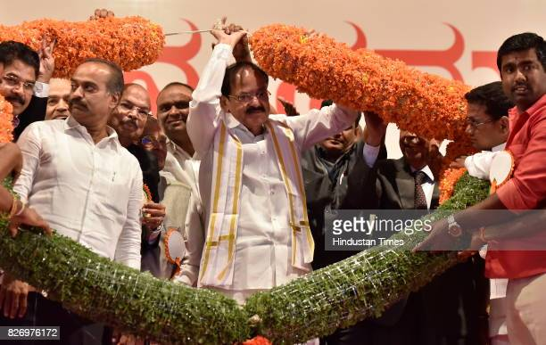 People greet elected Vice President M Venkaiah Naidu with a garland during a felicitation ceremony on August 6 2017 in Bengaluru India...