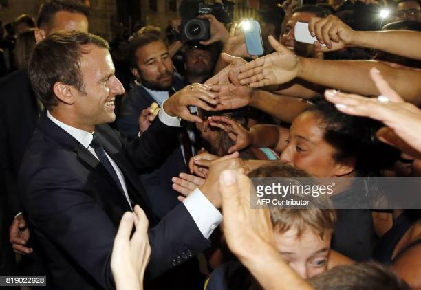 People greet French President Emmanuel Macron during his visit to the 'Rencontres d'Arles' annual photography festival in Arles southern France on...