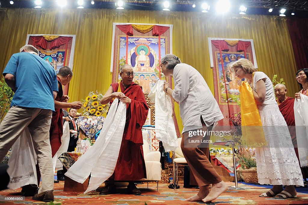 People greet the Dalai Lama (3rd L) during a public lecture at the the Modigliani Forum on June 15, 2014 in Livorno, Italy. The two-day meeting in Livorno drew about 10,000 visitors each day to the Forum to see the Dalia Lama explaining texts of Buddhist philosophers and teaching.