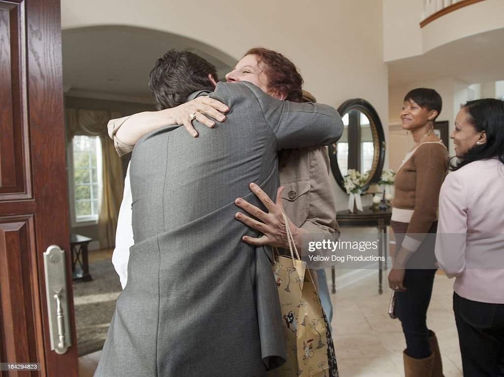 People greeting and embracing at a party : Stock Photo