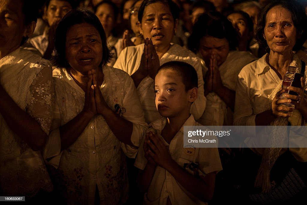 People grieve on the street after the the funeral fire was lit by King Norodom Sihamoni son of the late former King Norodom Sihanouk, and his mother, Queen Norodom Monineath during the cremation ceremony on February 4, 2013 in Phnom Penh, Cambodia. The former King's cremation ceremony comes on the fourth day of a seven day royal funeral ceremony and nearly four months since his death in Beijing last October. Foreign leaders from 16 countries attended the cremation ceremony.