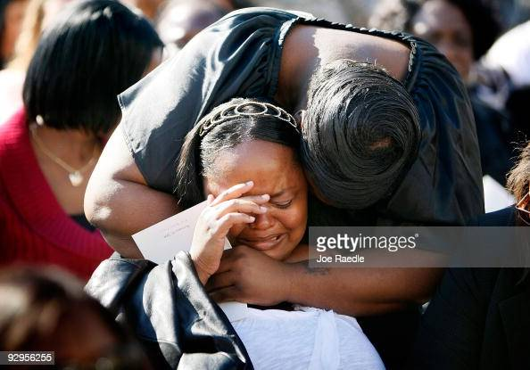 People grieve together before the start of the memorial service that US President Barack Obama and first lady Michelle Obama will attend for the...