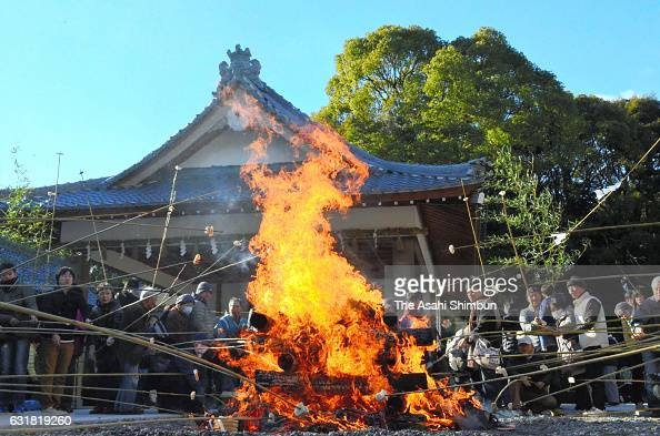 People grill 'mochi' Japanese rice cake on the bonfire which they burn ema wooden plaques and new year ornaments during the 'HitakiSai' fire festival...