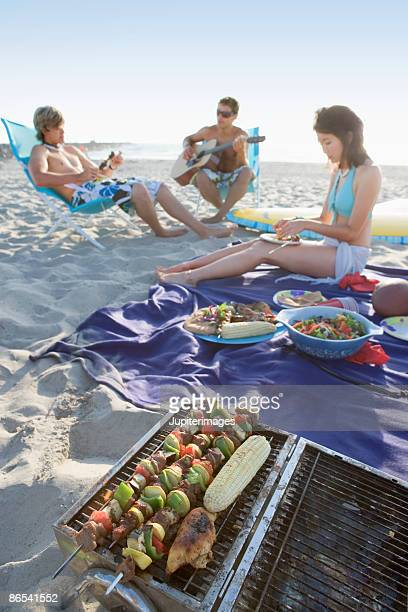 People grilling on beach