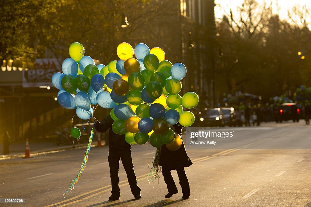 People hand out balloons on 72nd street before the commencement of the 86th Annual Macy's Thanksgiving Day Parade on November 22, 2012 in New York. Macy's donated tickets and transportation to this year's Thanksgiving Day Parade to 5,000 people from neighborhoods hardest hit by Superstorm Sandy.