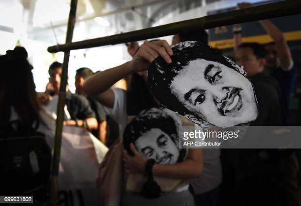 CORRECTION People hand out masks of Thai human rights activist Jatupat Pai Boonpattararaksa who was arrested in early December 2016 and charged with...