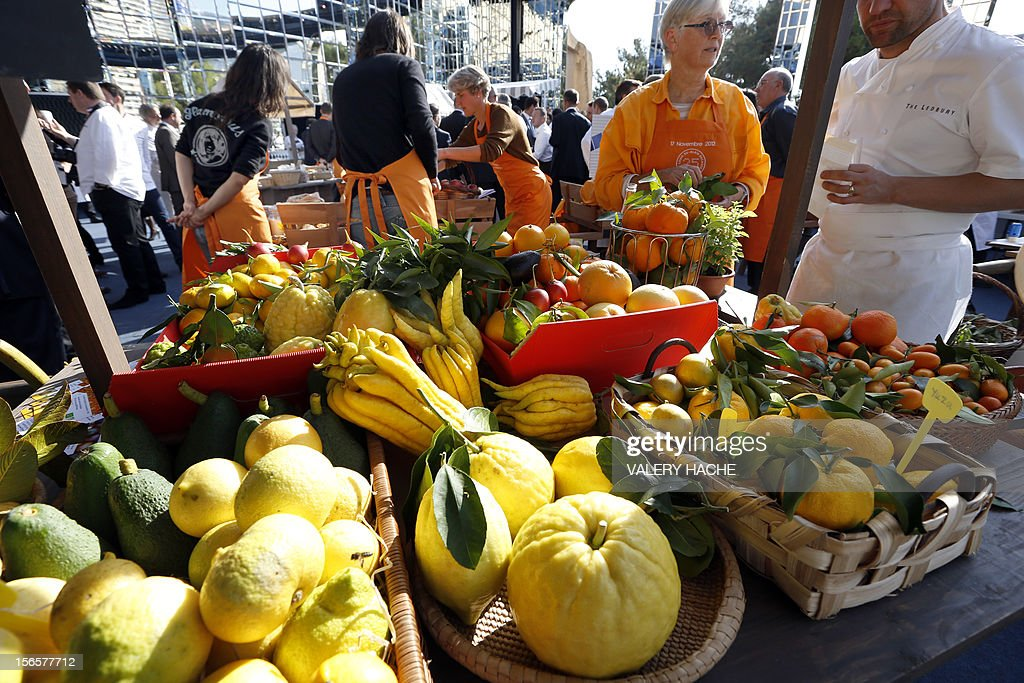 People handle stands at an ephemeral market during the festivities marking the 25th anniversary of French chef Alain Ducasse's restaurant 'Le Louis XV', on November 17, 2012 in Monaco.