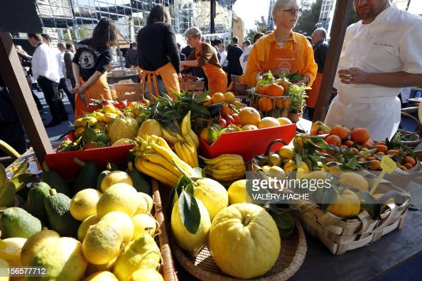 People handle stands at an ephemeral market during the festivities marking the 25th anniversary of French chef Alain Ducasse's restaurant 'Le Louis...