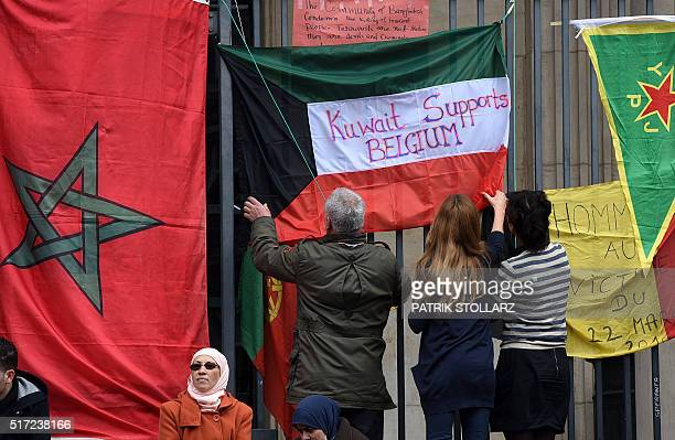 People hang a flag of Kuwait next to a flag of Morocco on the Place de la Bourse in central Brussels on March 24 two days after a triple bomb attack...