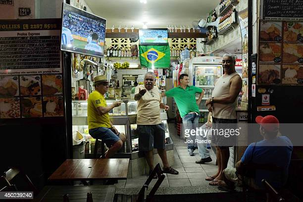 People hang out in a cafe as a soccer match plays on television on June 7 2014 in Rio de Janeiro Brazil Brazil continues to prepare to host the World...