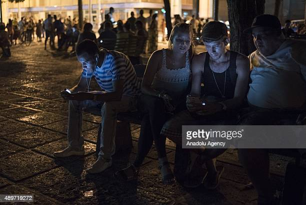 People hang out on a street corner to use a near by wifi hotspot to surf the internet on their smart phones in Havana Cuba on September 23 2015 Cuban...