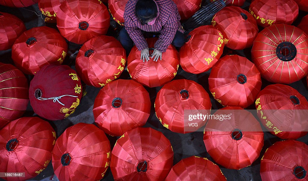 People hang red lanterns as the Chinese Lunar New Year is approaching on January 9, 2013 in Chengdu, Sichuan Province of China. Fall on February 10 this year, the Chinese Lunar New Year, also known as the Spring Festival, which is based on the Lunisolar Chinese calendar, will be celebrated from the first day of the first month of the lunar year and ends with Lantern Festival on the Fifteenth day.