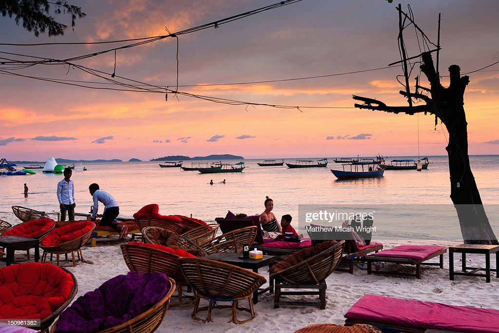 People have dinner on the beach at sunset. : Stock Photo