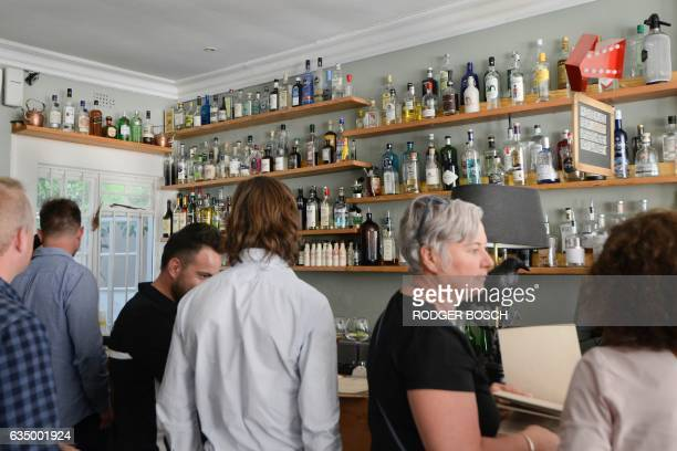 People have drink at the Mothers Ruin gin bar which stocks more 144 varieties of gin in the city centre of Cape Town on January 26 2017 Piling in for...