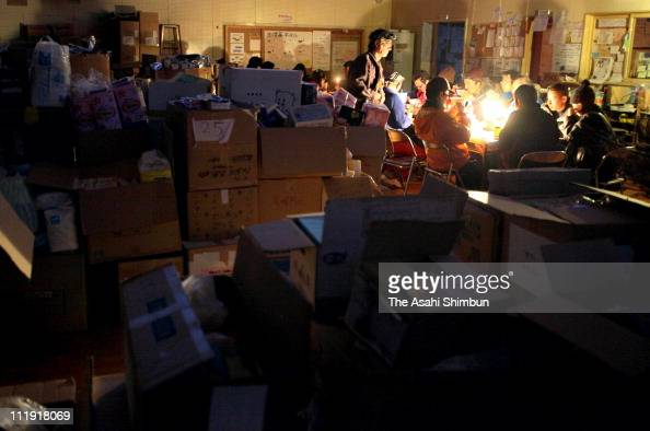 People have food under a candle light because of the power outage after the strong aftershock at an evacuation center on April 8 2011 in Tome Miyagi...