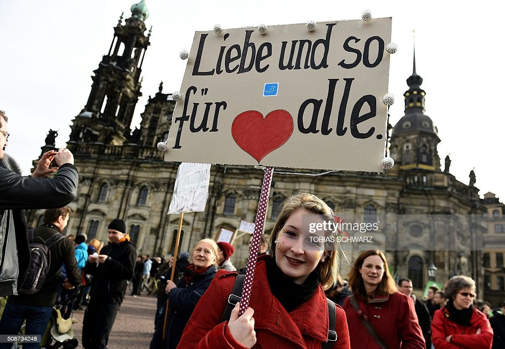 People have gathered in Dresden on February 6, 2016 to protest against a mass rally of the Pegida movement (Patriotic Europeans Against the Islamisation of the Occident). The placard reads 'Love for all'. / AFP / TOBIAS SCHWARZ