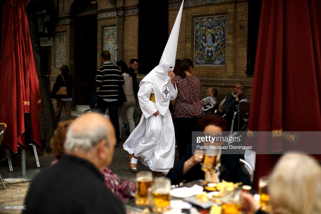 People have tapas and drinks outside a bar while penitent from 'San Gonzalo' brotherhood walks to the church to start a procession on April 14, 2014 in Seville, Spain. Easter week is traditionally celebrated with processions in most Spanish towns.