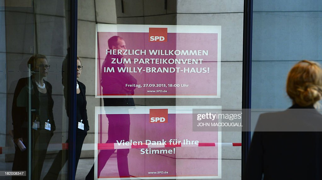 People have their image reflected on the glass door of German Social Democratic Party (SPD) headquarters on September 27, 2013 where a meeting on a 'grand coalition' takes place. Germany's opposition Social Democrats hold a mini-party conference to discuss behind closed doors overtures by Chancellor Angela Merkel for a left-right 'grand coalition' after her conservatives won weekend elections but fell short of an outright majority MACDOUGALL