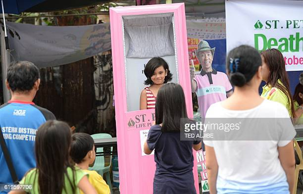 People have their photos taken on a mock coffin being advertised for a funeral parlor company outside a public cemetery during the annual religious...